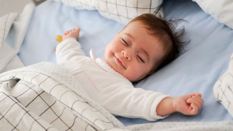 Happy toddler sleeping in a bed