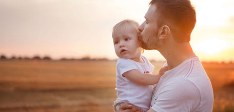 father and baby in front of a sunset