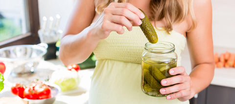 pregnant woman eating a jar of pickles