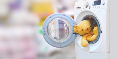 Teddy bear hanging out of a washing machine