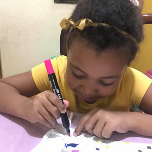 Child coloring in mask using fabric markers