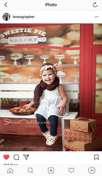 Toddler sitting on a bench in front of bakery with an Everything Dawn Bakery Candles fake cherry pie