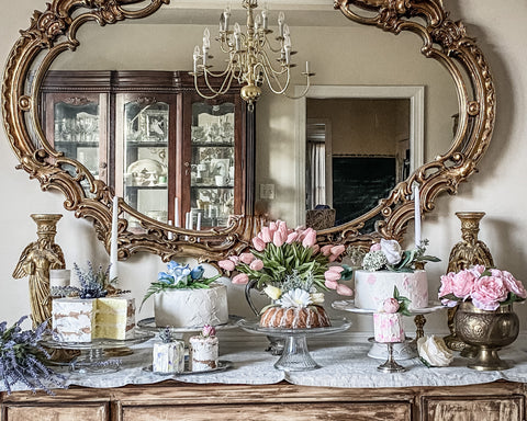 Faux cakes on buffet table with tulips and gold vintage mirror on wall behind