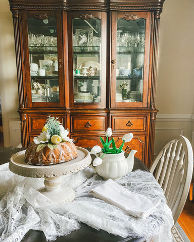 Faux cake on table with linens and china hutch behind