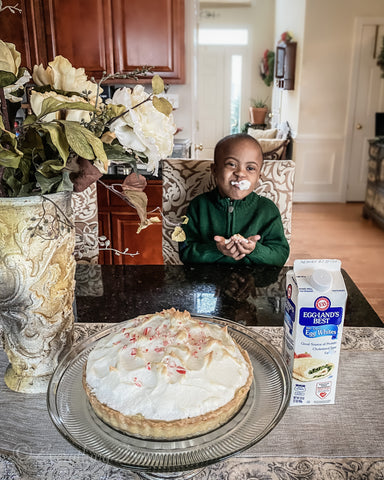 Eggland's Best egg whites with boy eating meringue and pie sitting on counter in front