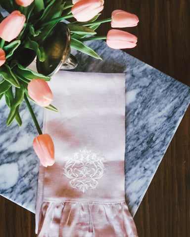 spring pink tulips on marble with pink linen ruffle towel