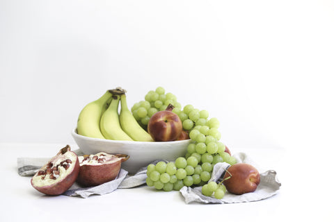 bowl of fresh bananas figs and grapes on linen with figs surrounding