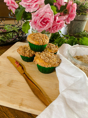 muffins on cutting board with knife and cloth with pink roses in a vase behind