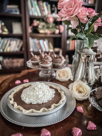 chocolate pie with whipped cream on dessert table with pink roses