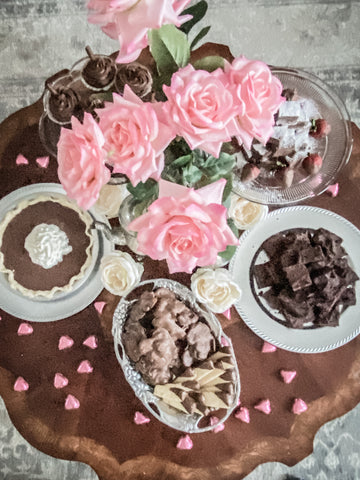 Chocolate bar with pin roses, pie and chocolates on table