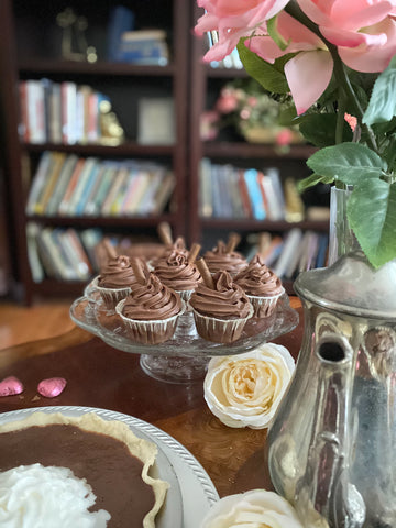 Chocolate cupcakes on table with pink flowers