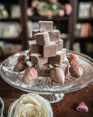 homemade fudge on crystal cake stand with chocolate dipped strawberries