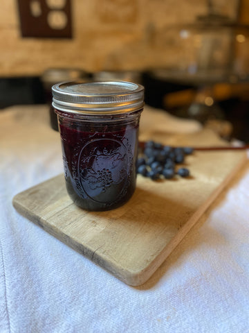 Blueberry jam on wooden board with blueberries