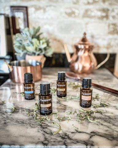 Far & Wild essential oils on white marble counter with copper teapot behind