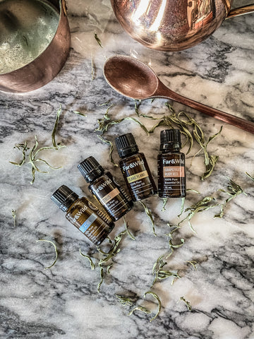 flatlay of far and wild essential oils on white marble counter with wooden spoon