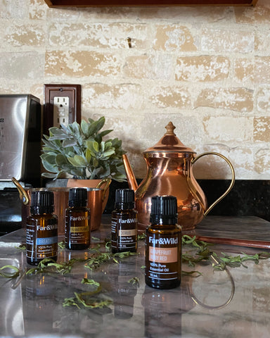 ruby red grapefruit oil on marble counter top with copper teapot behind