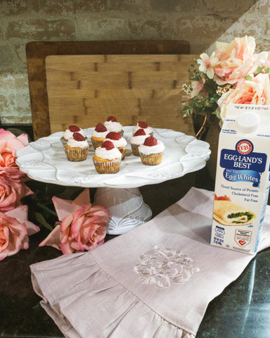 raspberry mojito cupcakes on white cake stand with pink linen kitchen towel and eggland's best 100% egg whites carton with pink flowers surrounding