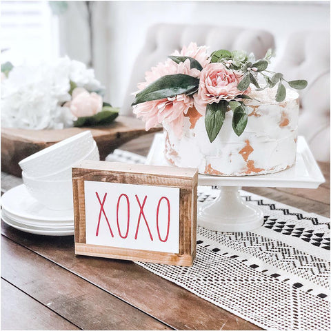 pink and white floral cake with xoxo sign