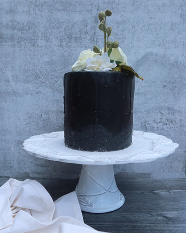 Black drip cake faux cake with white silk flowers on top