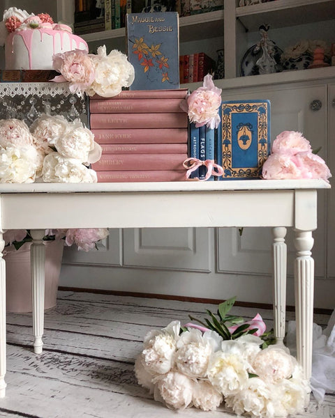 table with books flowers and faux cake