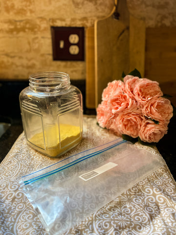 cornmeal and a zip lock bag with faux flowers on counter top