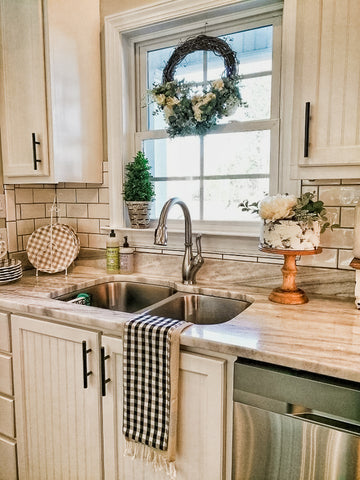 faux cake in kitchen beside sink with wreath in window