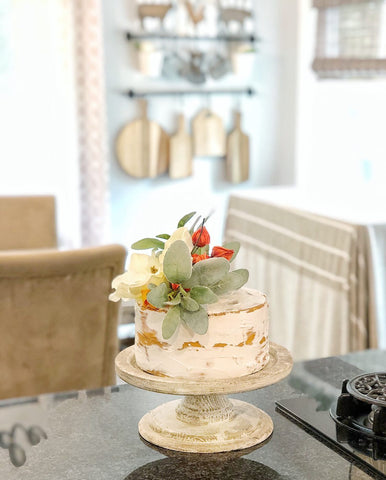 faux cake with orange flowers and greenery on kitchen counter with wooden boards on wall behind