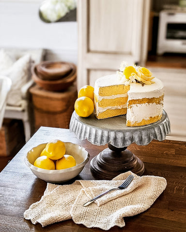 faux lemon cake on rustic metal cake stand with lemons surrounding