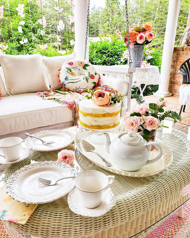 faux cake with pink flowers on patio table with white tea set