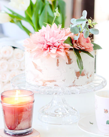 faux cake with pink dahlia and greenery and pink glowing candle in front