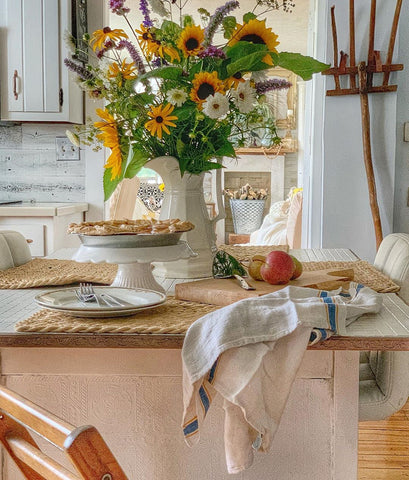 Faux apple pie on counter with a vase of sunflowers