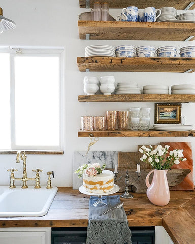 Pink Faux cake on wooden counter below wooden floating shelves
