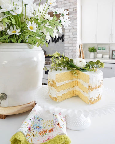 Faux cake with slice out on white cake stand with large vase of daisies