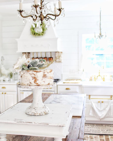 faux cake on kitchen table with antique gold candelabra chandelier hanging over