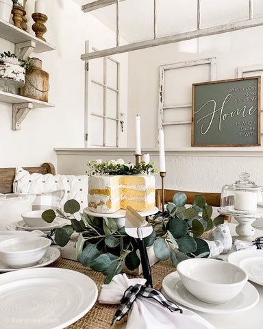 faux cake centerpiece on dining table with white dishes
