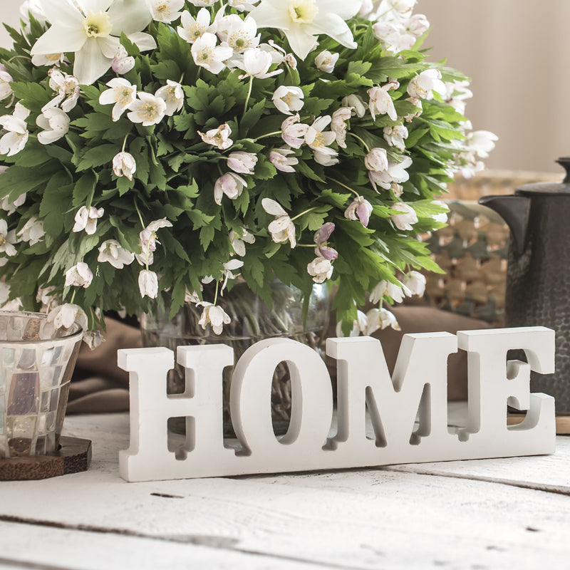 Block letters spelling HOME in front of a white wood tea tray with a tea cup and a vase full of lavender and a cozy blanket nearby