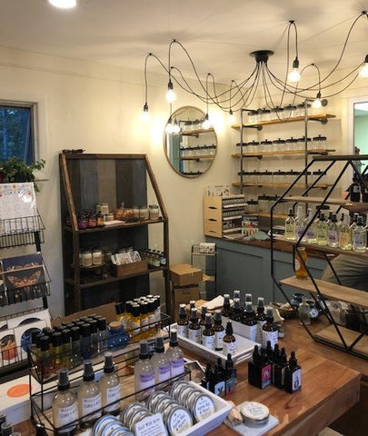 Inside of store with glass jars lining wall shelves, chandelier, herbal products, teas