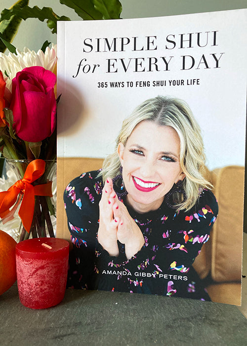 Simple Shui for Every Day 365 Ways to Feng Shui Your Life book cover next to a red candle, orange, and vase of pink, orange, and white flowers