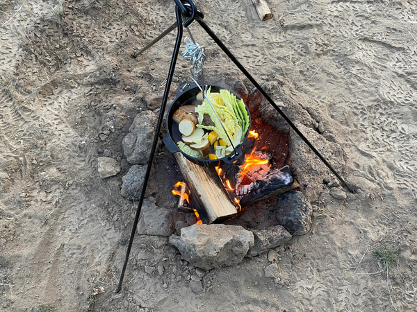 Cooking pot roast over fire in dutch oven.