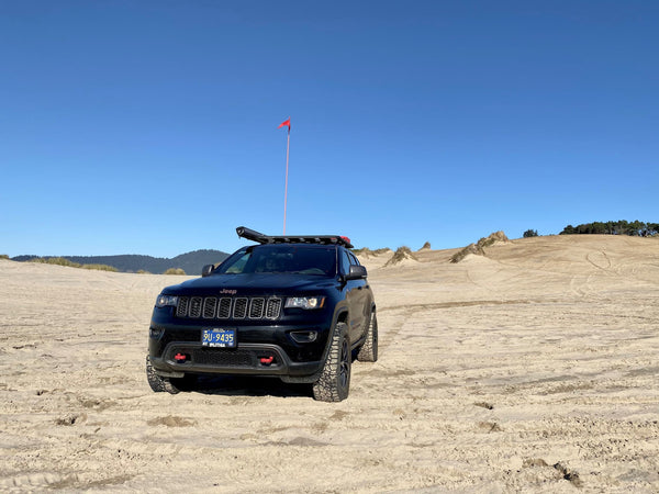 Rugged Jeep Grand Cherokee playing on the dunes.