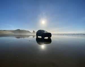 Jeep Grand Cherokee Trailhawk with Rhino Rack Pioneer Platform on sunny beach, on reflective sand.