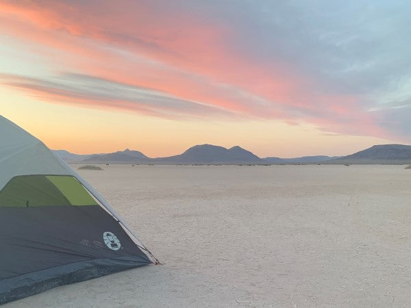 Ground tent on vast open desert playa with a beautiful, colorful sunset.