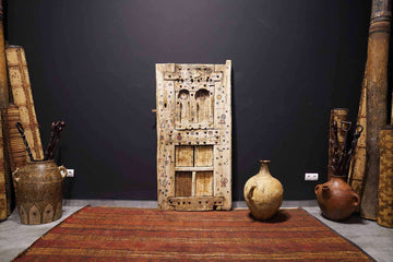 jewish Antique Moroccan Door next to different decor and vintage rugs at an art gallery