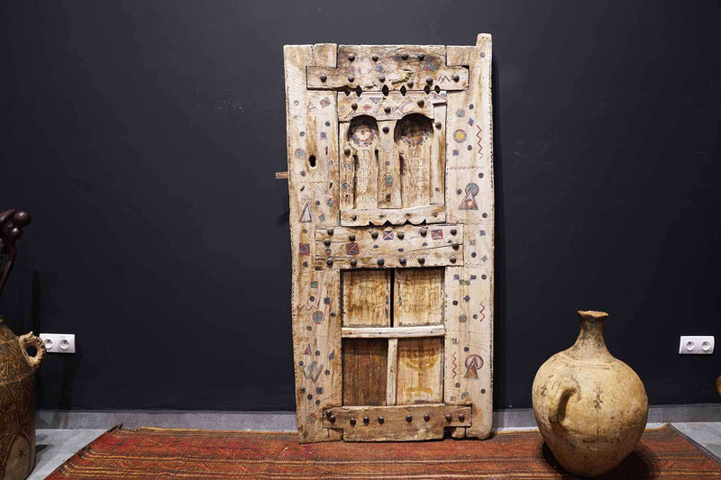 Antique Moroccan Door next to a moroccan pot and rugs