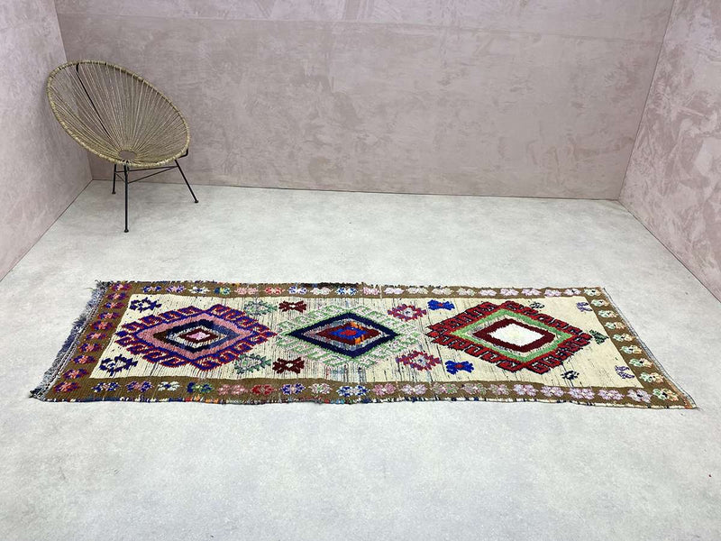 An orange Vintage Moroccan Rug on marble flooring.