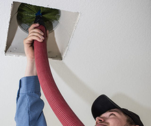 Load image into Gallery viewer, PVHAC home performance expert cleaning an air duct in a customer's home