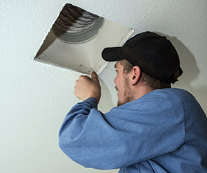 PVHAC home performance expert sealing an air duct in a customer's home