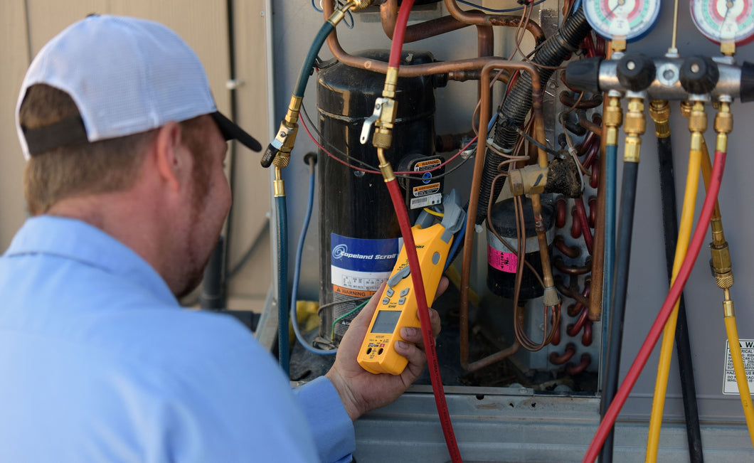 PVHAC service technician reading amp draws and pressures on a unit during a service call