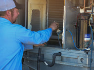 PVHAC service technician cleaning the coil housing of a unit during a maintenance visit