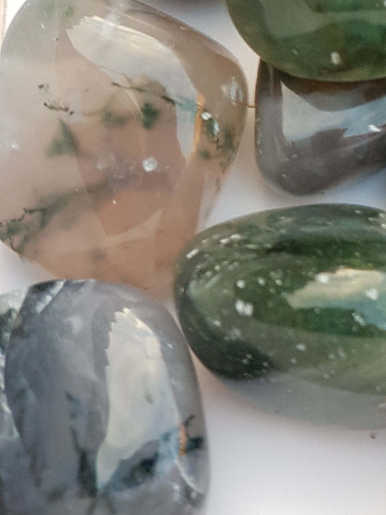 a close up of three tumbled pieces of green moss agate. The pieces are translucent and clear. Inside the stone are strands of a dark green material.